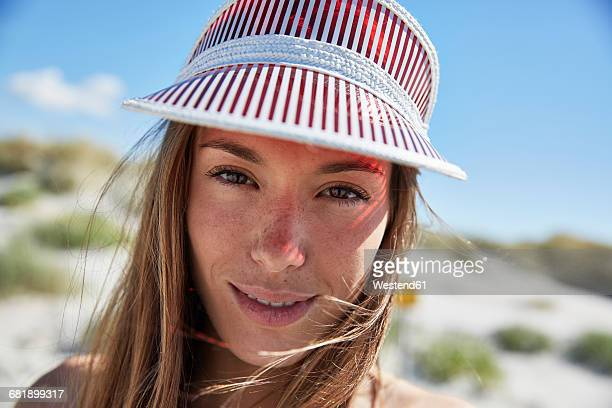 Portrait of smiling young woman wearing sun visor on the beach