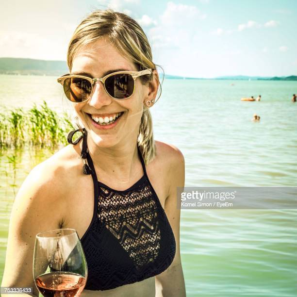 Portrait Of Smiling Young Woman Wearing Sunglasses Against Lake