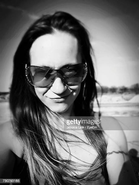 Portrait Of Smiling Young Woman Wearing Sunglasses On Sunny Day