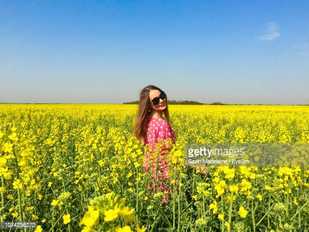 portrait of smiling young woman wearing sunglasses standing amidst yellow flowers on field against clear sky during sunny day - lady madeleine stock-fotos und bilder