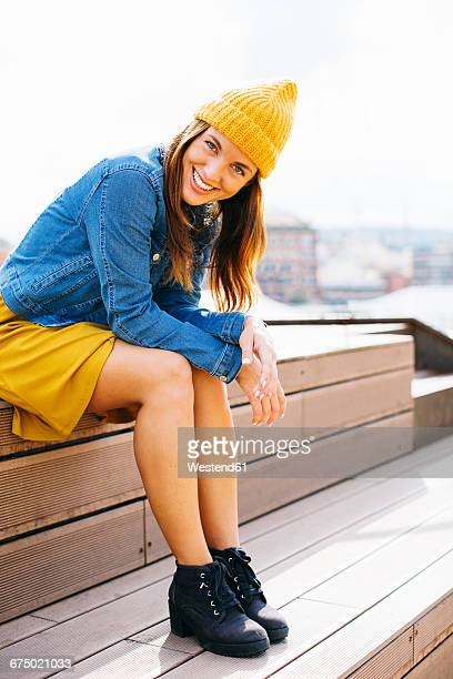 Portrait of smiling young woman wearing yellow cap sitting on steps