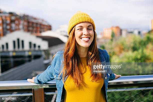 Portrait of smiling young woman wearing yellow cap sticking out tongue