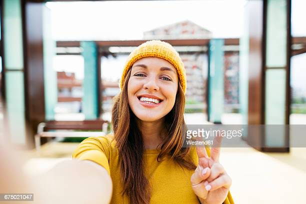 portrait of smiling young woman wearing yellow clothes taking selfie - self portrait stock pictures, royalty-free photos & images