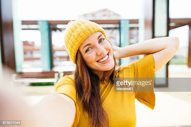 portrait of smiling young woman wearing yellow clothes taking selfie - 首をかしげる ストックフォトと画像