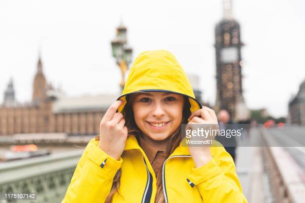 portrait of smiling young woman wearing yellow raincoat on a rainy day, london, uk - raincoat stock pictures, royalty-free photos & images