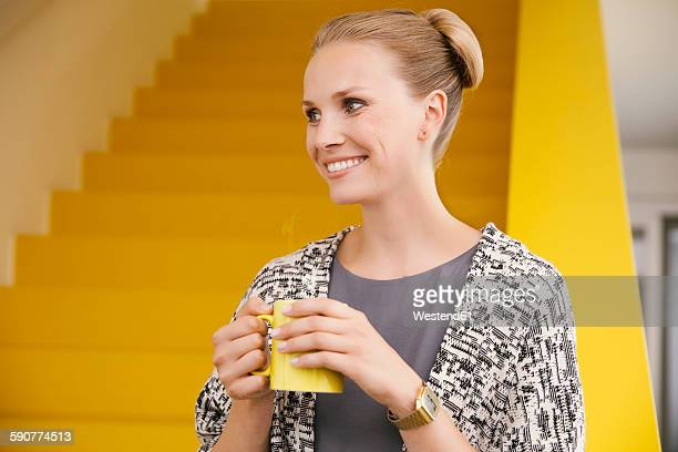 portrait of smiling young woman with a hot beverage in front of yellow stairs - up do stock pictures, royalty-free photos & images