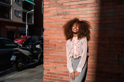 Portrait of smiling young woman with afro hairdo leaning against brick wall in the city - gettyimageskorea