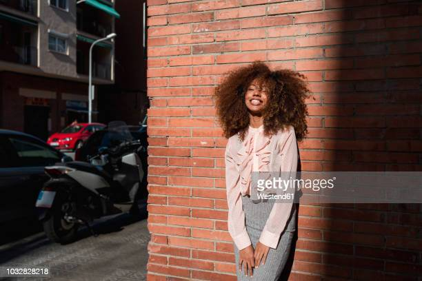 portrait of smiling young woman with afro hairdo leaning against brick wall in the city - afro frisur stock-fotos und bilder