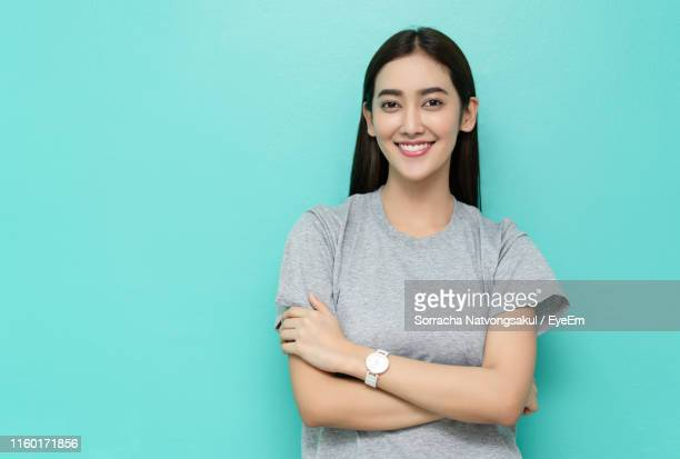 portrait of smiling young woman with arms crossed against turquoise background - ターコイズカラーの背景 ストックフォトと画像