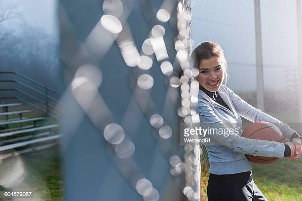 Portrait of smiling young woman with basketball leaning against mesh wire fence on a sports field