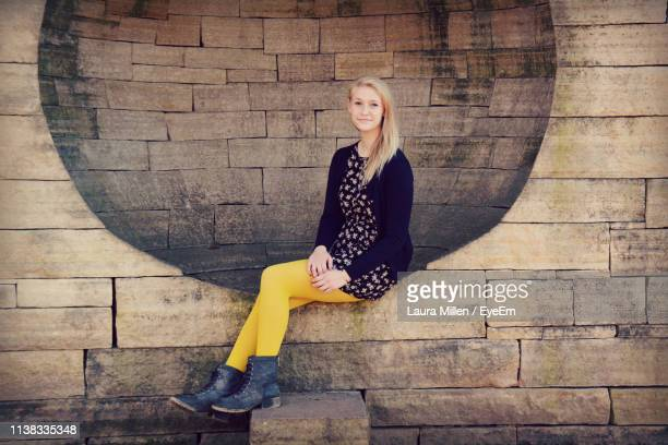 portrait of smiling young woman with blond hair sitting against wall - laura belli foto e immagini stock