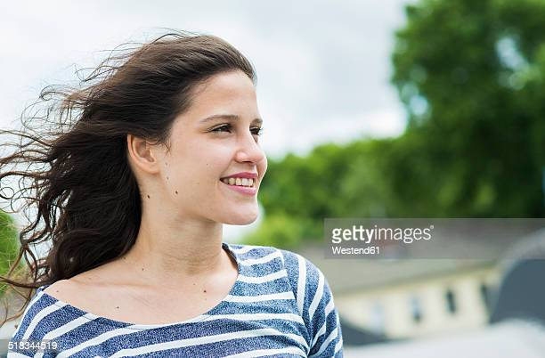 Portrait of smiling young woman with blowing hair