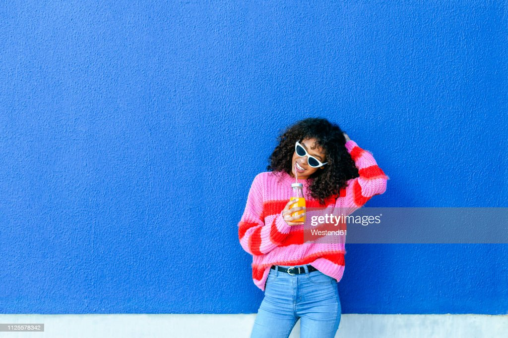 Portrait of smiling young woman with bottle of orange juice standing in front of blue wall : Stock Photo