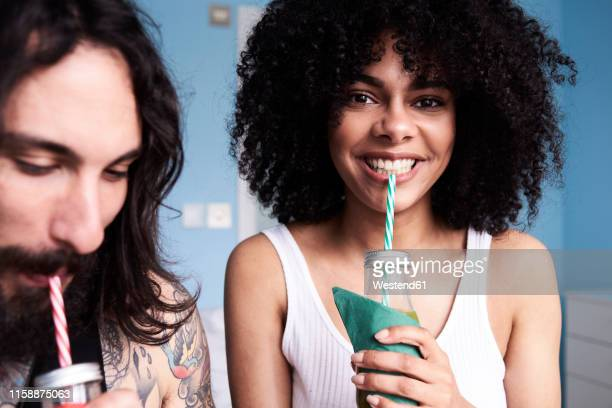 portrait of smiling young woman with boyfriend drinking smoothie - juice drink stock pictures, royalty-free photos & images