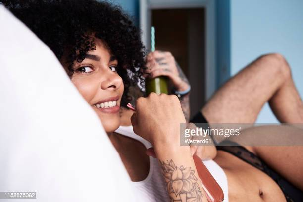 portrait of smiling young woman with boyfriend  lying in bed drinking smoothie - frau in slip stock-fotos und bilder
