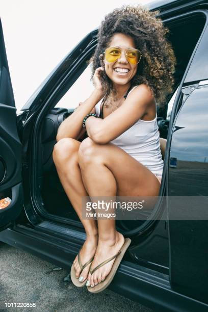 portrait of smiling young woman with brown curly hair sitting in car, wearing sunglasses, white vest and flip flops. - sandal stock pictures, royalty-free photos & images