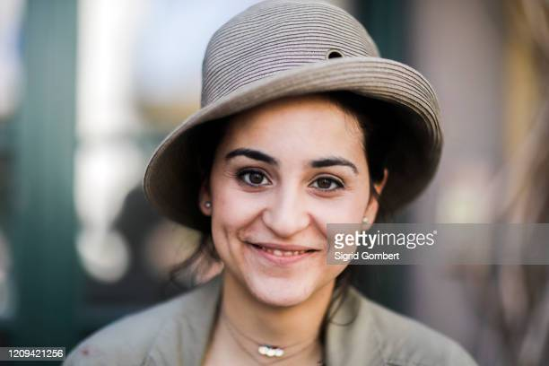 portrait of smiling young woman with brown hair wearing hat, looking at camera. - sigrid gombert stock pictures, royalty-free photos & images