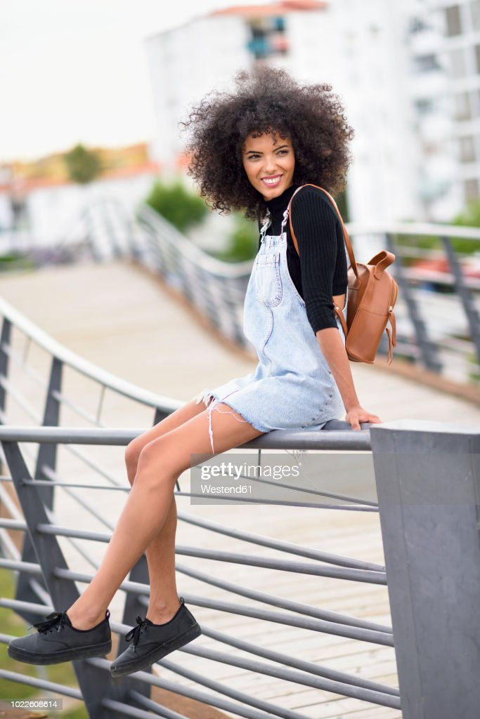Portrait of smiling young woman with brown leather backpack sitting on railing of a bridge : Stock Photo