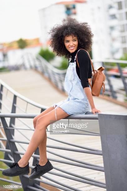 portrait of smiling young woman with brown leather backpack sitting on railing of a bridge - leather dress stock pictures, royalty-free photos & images