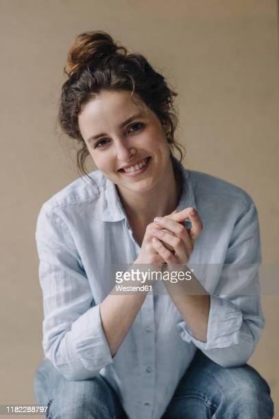 portrait of smiling young woman with bun - blouse stockfoto's en -beelden