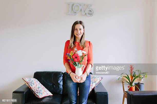 Portrait of smiling young woman with bunch of flowers in her living room