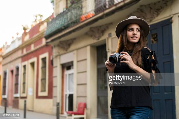 Portrait of smiling young woman with camera outdoors