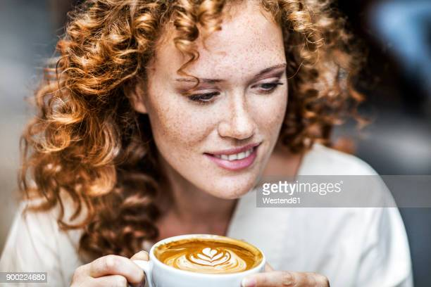 Portrait of smiling young woman with Cappuccino