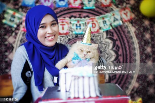 portrait of smiling young woman with cat during birthday celebration - happy birthday cat stock photos and pictures