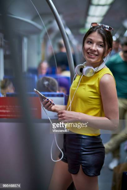 portrait of smiling young woman with cell phone and headphones in underground train - seitenblick stock-fotos und bilder