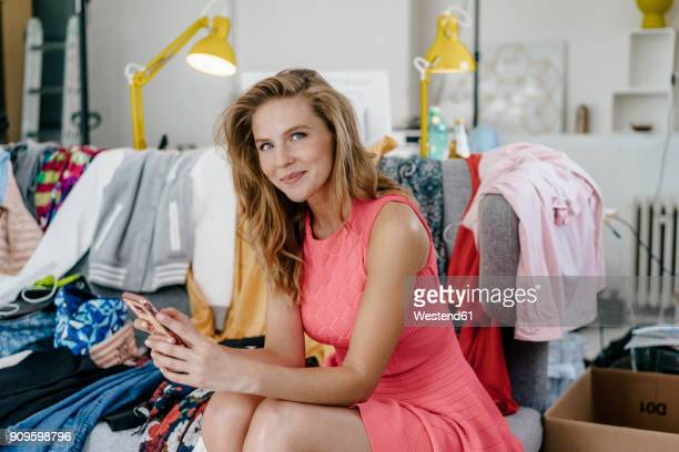 Portrait of smiling young woman with cell phone surrounded by fashion