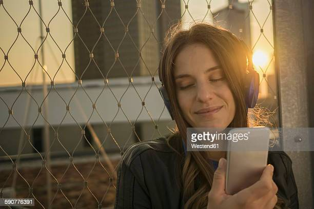 Portrait of smiling young woman with closed eyes hearing music with headphones at backlight
