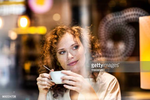 portrait of smiling young woman with coffee cup behind windowpane of a coffee shop - cafe imagens e fotografias de stock
