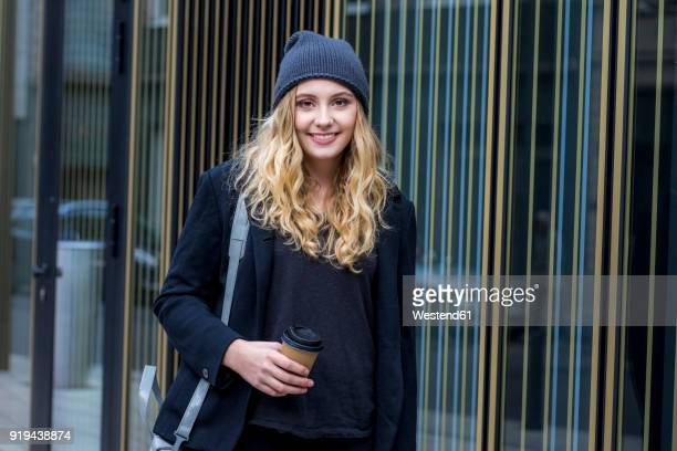 portrait of smiling young woman with coffee to go in autumn - student stock-fotos und bilder