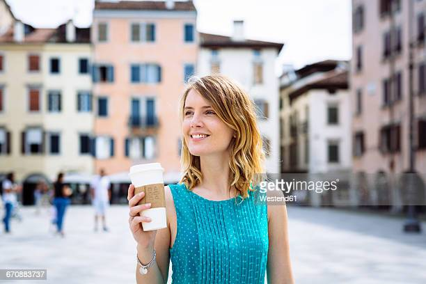Portrait of smiling young woman with coffee to go