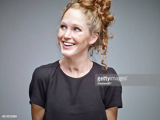 portrait of smiling young woman with curly blond hair in front of grey background - haar naar achteren stockfoto's en -beelden