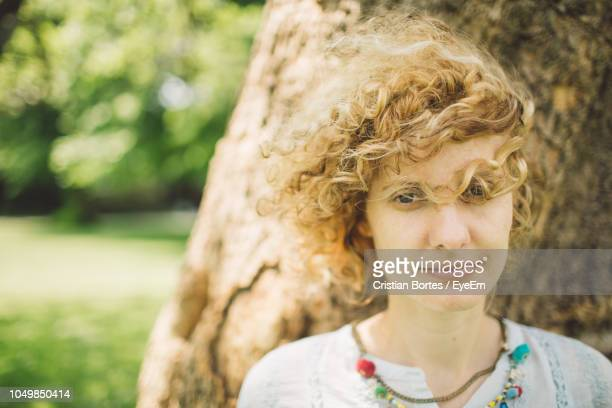 portrait of smiling young woman with curly blond hair - bortes stockfoto's en -beelden