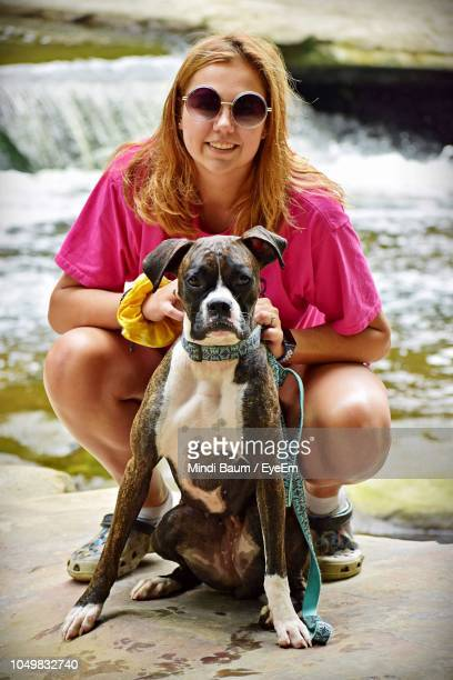portrait of smiling young woman with dog against river - baum stock pictures, royalty-free photos & images