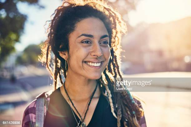 Portrait of smiling young woman with dreadlocks in the city