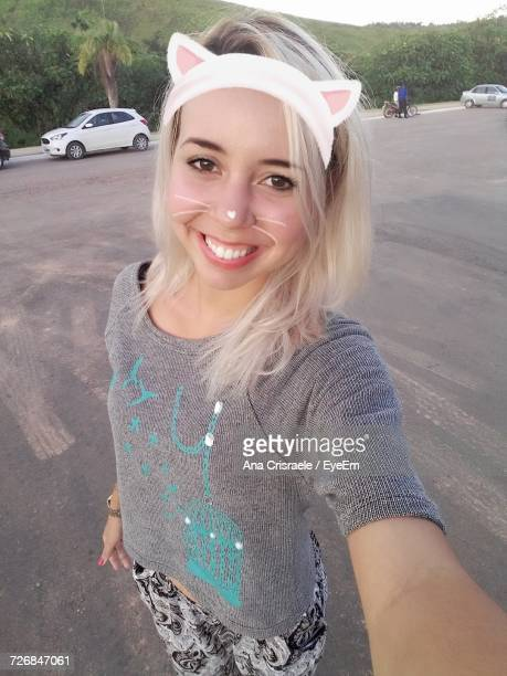 portrait of smiling young woman with face paint standing on road - cat costume stock photos and pictures