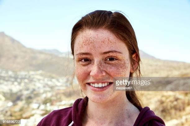 portrait of smiling young woman with freckles outdoors - só uma mulher jovem - fotografias e filmes do acervo