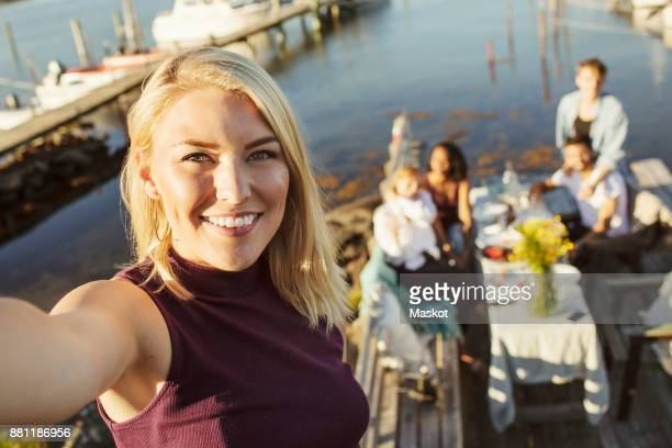 Portrait of smiling young woman with friends in background at jetty