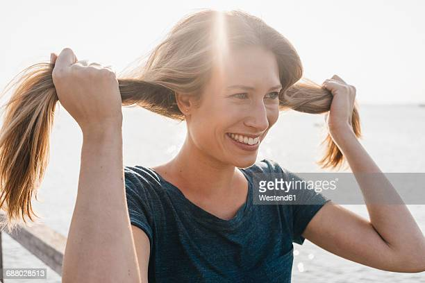 Portrait of smiling young woman with hand in her hair on jetty