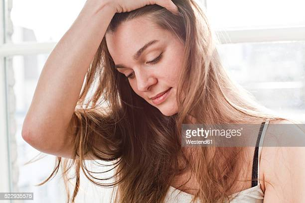 portrait of smiling young woman with hand in her hair - 髪に手をやる ストックフォトと画像