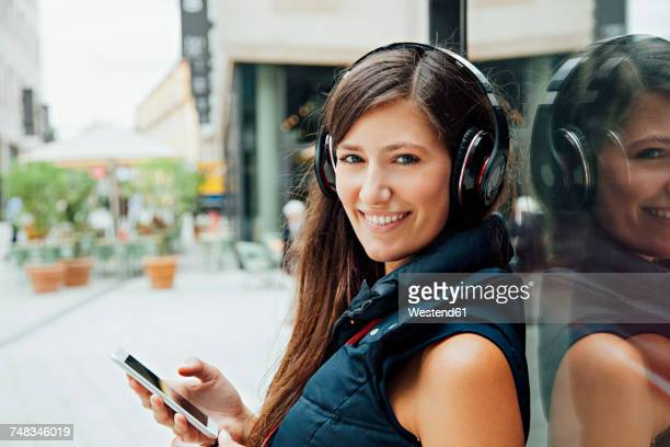 Portrait of smiling young woman with headphones and cell phone in the city