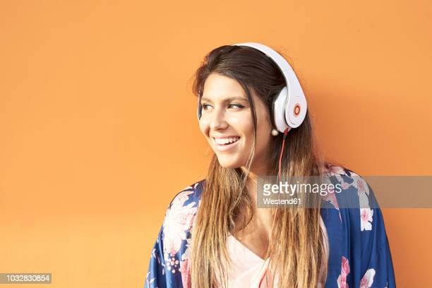 portrait of smiling young woman with headphones in front of orange background - orange background stock pictures, royalty-free photos & images