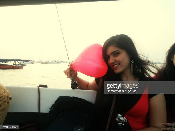 Portrait Of Smiling Young Woman With Heart Shape Balloon In Sailboat On Sea