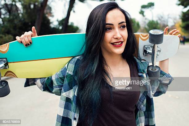 Portrait of smiling young woman with longboard on her shoulders