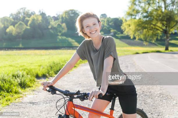 Portrait of smiling young woman with mountain bike