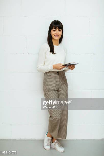 portrait of smiling young woman with notebook standing at brick wall - encuadre de cuerpo entero fotografías e imágenes de stock