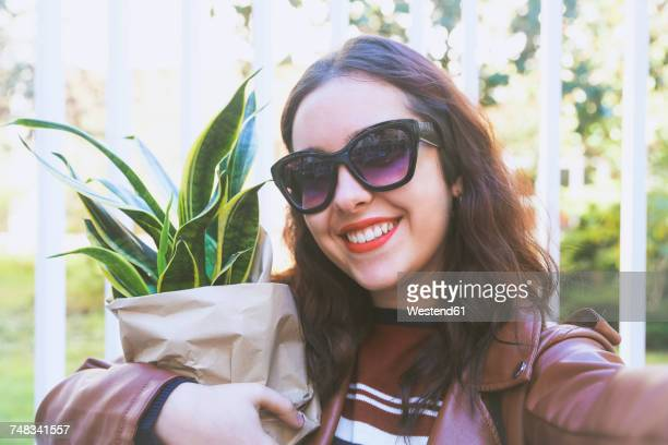 Portrait of smiling young woman with potted plant taking selfie with smartphone